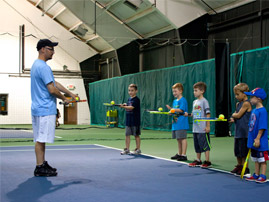 Instructor helping junior tennis players
